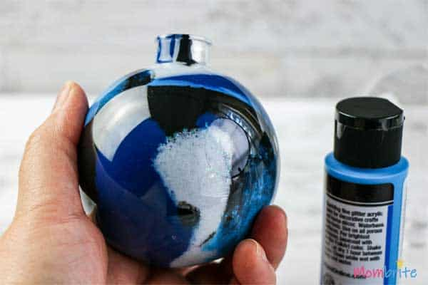 Add dark blue paint in plastic ornament balls